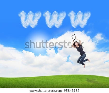 Young beauty happy jump and showing tablet pc in the air on meadow with www cloud sky background , model is a cute asian, for cloud computing concept - stock photo