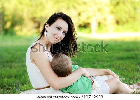 Young beauty mother breast feeding her cute baby son outdoors in the park - stock photo
