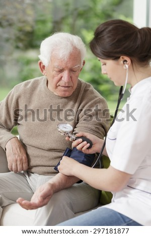 Young beauty nurse holding blood pressure gauge - stock photo