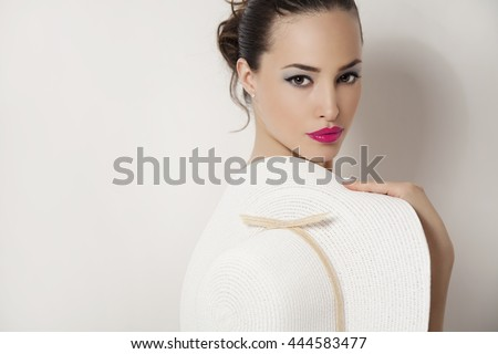 young beauty portrait with pink lips holding summer white hat, studio - stock photo