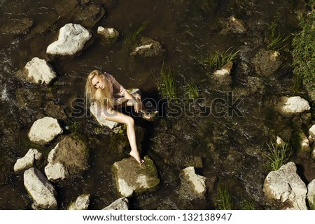 young beauty relaxes on the river bank - stock photo