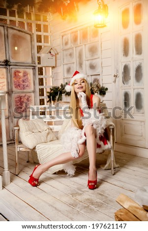 Young beauty smiling santa woman near the Christmas tree. Fashionable luxury girl celebrating New Year. Beautiful luxury trendy blonde.  - stock photo