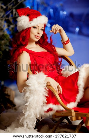 Young beauty smiling santa woman near the Christmas tree. Fashionable luxury girl celebrating New Year. Beautiful luxury trendy redhead lady. - stock photo