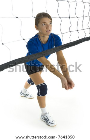 Young, beauty volleyball player. Standing in front of net and preparing to take the ball. White background. Whole body, side view - stock photo