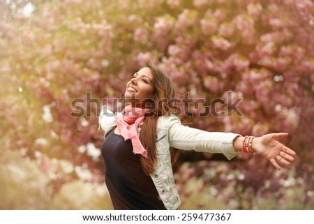 young beauty with arms wide open under blooming cherry tree - stock photo