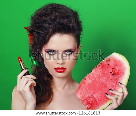 Young beauty woman holding watermelon over green background - stock photo