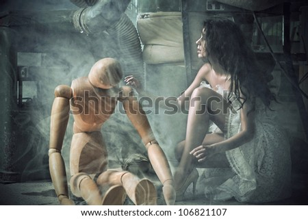 Young beauty woman hugging a wooden dummy - stock photo