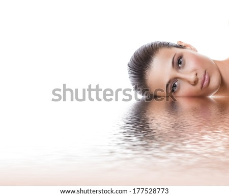 Young beauty woman lying down, isolated on white background - studio shot. Young female with healthy fresh skin, skincare concept - stock photo