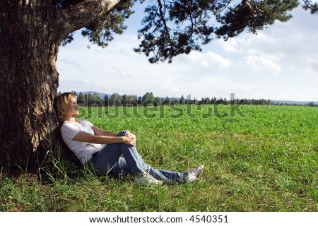 young beauty woman sit under alone tree in field under blue sky and clouds - stock photo