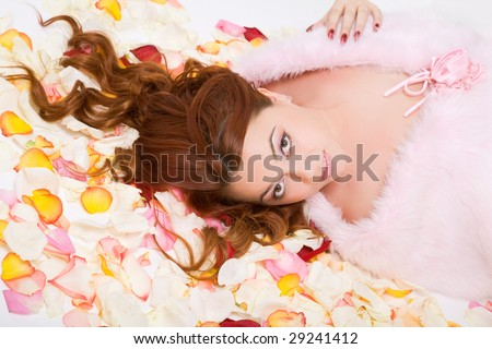 young beauty woman with long hair lying on petals - stock photo