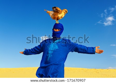 Young Berber in Traditional Desert Dress proudly posing with his Falcon Bird  - stock photo