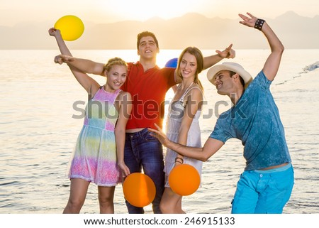 Young Best Buddies Enjoying at the Beach Side with Balloons. Captured During Sunset time. - stock photo