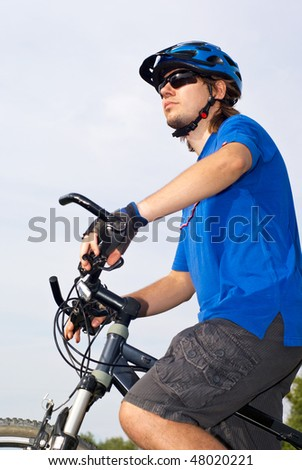 young bicyclist in a blue helmet ride bicycle on nature - stock photo