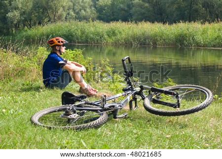 young bicyclist in helmet sitting on a green grass near the bicycle - stock photo