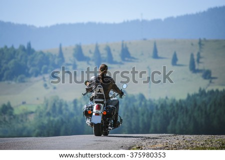 Young biker with long hair on mountainous road. Man is riding his custom made travel motorbike on highway. View from the back. - stock photo