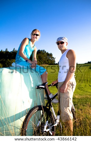 young bikibg couple having rest in the field - stock photo