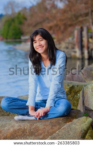 Young biracial teen girl in blue shirt and jeans sitting on large boulder or rocks along rocky lake shore, smiling and reclining - stock photo