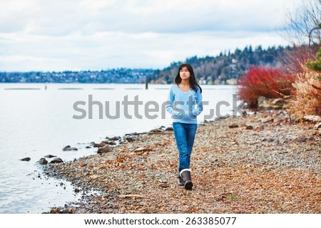 Young biracial teen girl in blue shirt and jeans walking along rocky shoreline of lake in early spring or fall - stock photo