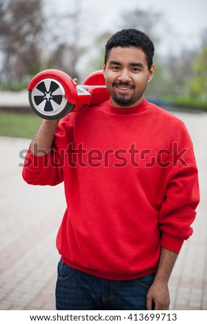 Young black African guy with a modern red electric mini hover board scooter in a park outdoors. Popular new urban transport that makes no air pollution to the city atmosphere.  - stock photo