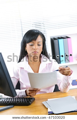 Young black business woman reading document at desk in office - stock photo