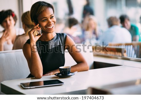 Young black businesswoman talking on the phone in coffee shop - stock photo