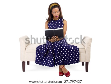 young black female in vintage style reading a book and sitting on a chaise lounge - stock photo