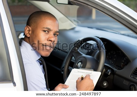 Young Black inspector, business man inspecting car, doing a checklist - stock photo
