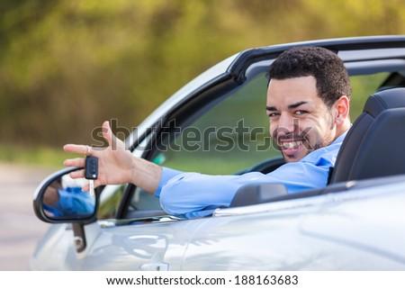 Young black latin american driver holding car keys driving his new car - stock photo