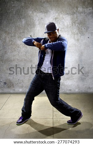 young black male dancing hip hop style in an urban setting.  he is wearing a blue hoodie and is on a concrete background - stock photo