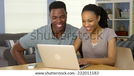 Young black man and woman using laptop together at desk - stock photo
