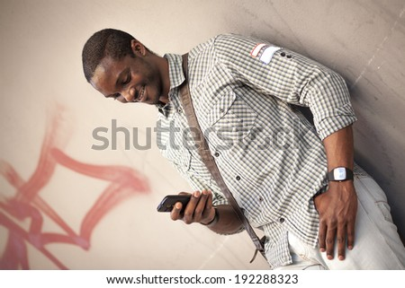 Young black man checking messages on his smart phone - stock photo