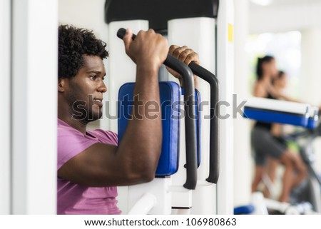 Young black man exercising pectoral muscles in fitness club, with people working out on cyclette in background - stock photo