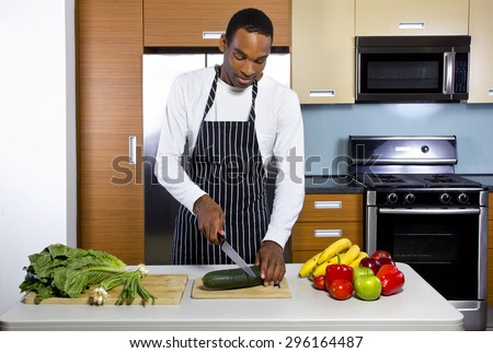 Young black man learning how to cook in a domestic kitchen with fruits and vegetables. He looks like a novice or amateur and trying to learn how to prepare healthy food. - stock photo