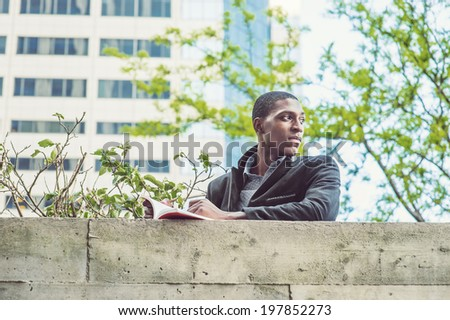 Young black man reading outside. A young black college student is standing by the top of the wall outside a building, reading a book, looking around, waiting for you.  - stock photo