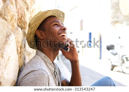 Young black man smiling and talking on mobile phone outside - stock photo
