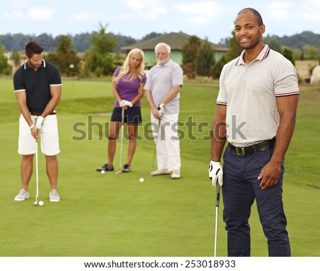 Young black man smiling happy on golf course, holding golf club. - stock photo
