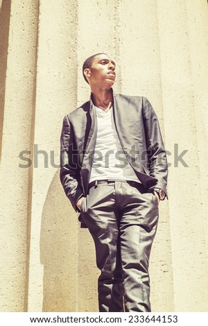 Young black man thinking outside. Wearing a white under wear, fashionable jacket, two hands in pockets, a young black college student is standing under strong sun light, looking forward, thinking. - stock photo