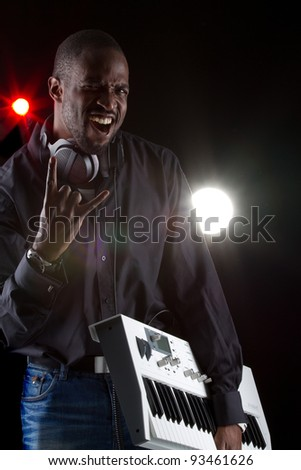 Young black man with a keyboard and headphones over black background. - stock photo