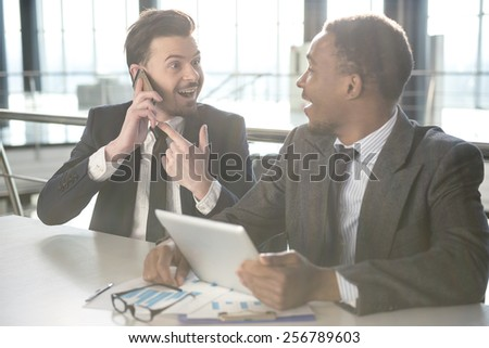 Young black smiling businessman is looking at his partner who talking by phone. - stock photo