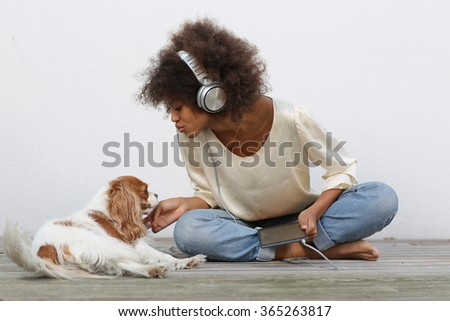 young black student using electronics on desk with her dog - stock photo