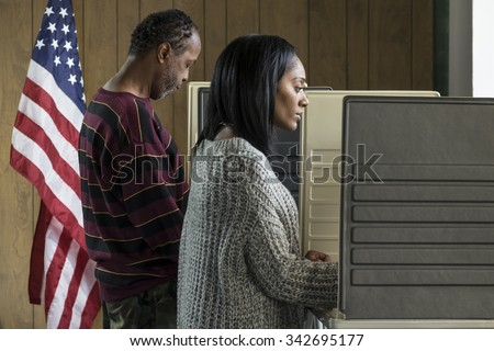 Young black woman and older black male voting in a booth - stock photo