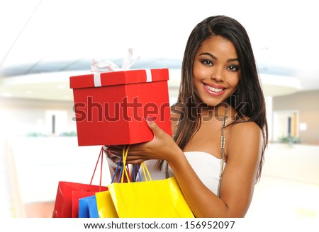 Young Black woman holding bags and a box inside a mall - stock photo