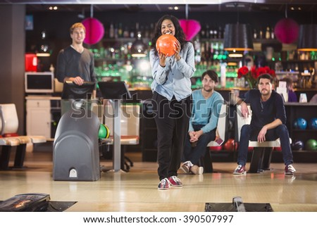 Young black woman holds the bowlingball up to throw it, with her friends in the background - stock photo