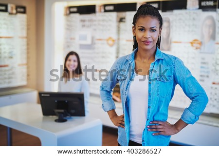 Young black woman smiling standing in her store with a colleague in backgorund - stock photo
