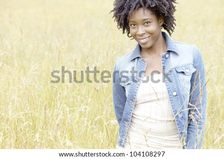 Young black woman standing in a yellow field, smiling. - stock photo