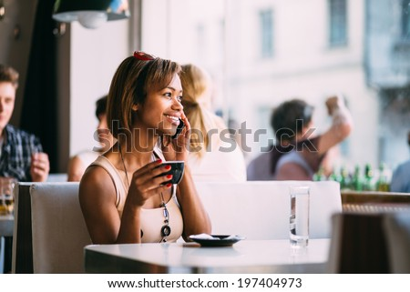 Young black woman talking on the phone in coffee shop - stock photo
