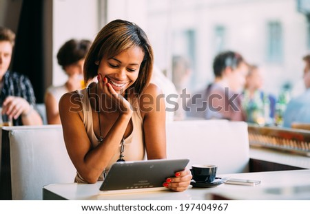 Young black woman using tablet computer in coffee shop - stock photo