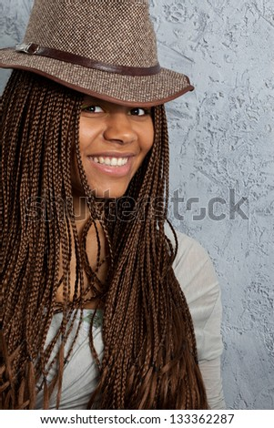 young black woman with African braids in a hat - stock photo