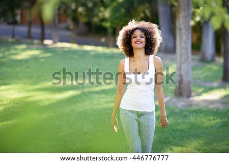 Young black woman with afro hairstyle smiling in urban park. Mixed girl wearing white t-shirt and blue jeans walking on the grass. - stock photo