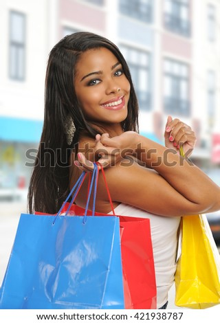Young black woman with shopping bags outside a mall - stock photo